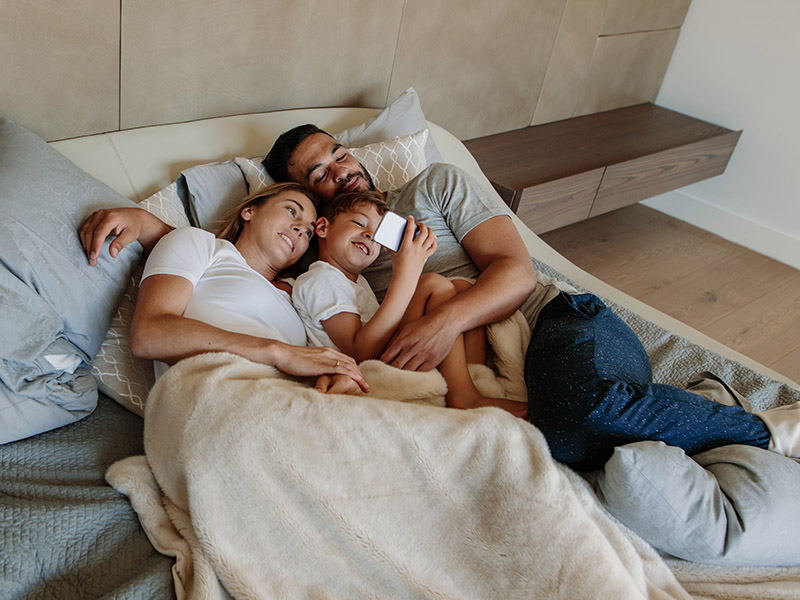 Young family in bedroom looking at cell phone